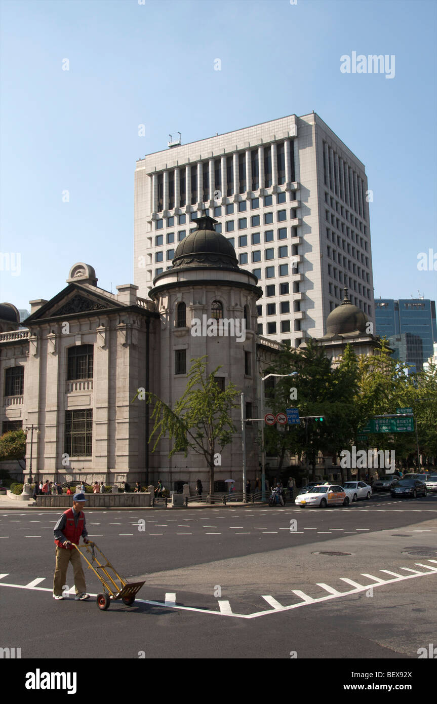 Mna wheeling a sack barrrow past the Bank of Korea Building in the centre of Seoul, capital of South Korea. October - Stock Image