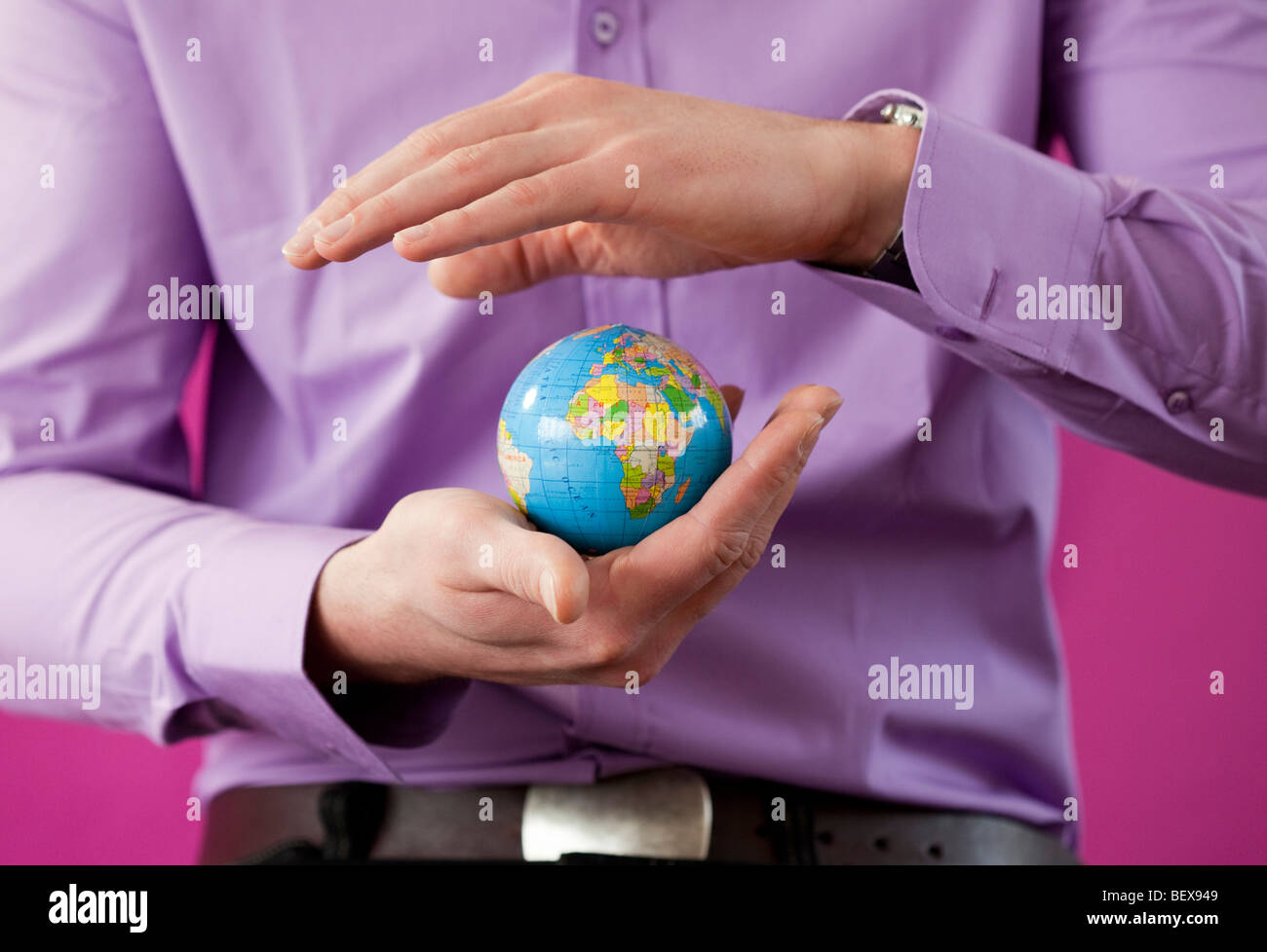 Young man holding a little globe - Stock Image
