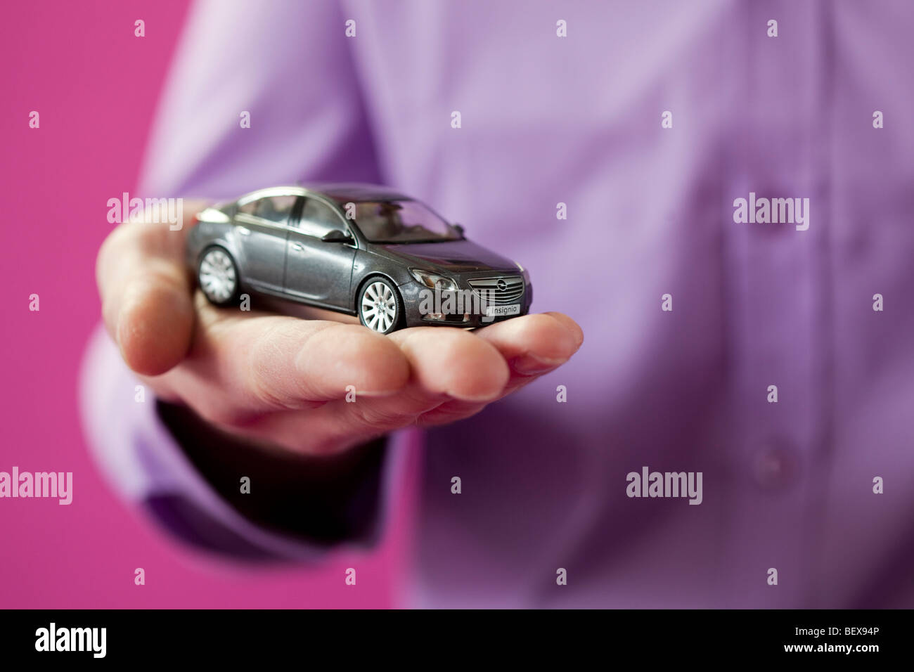 Young man holding a toy car - Stock Image