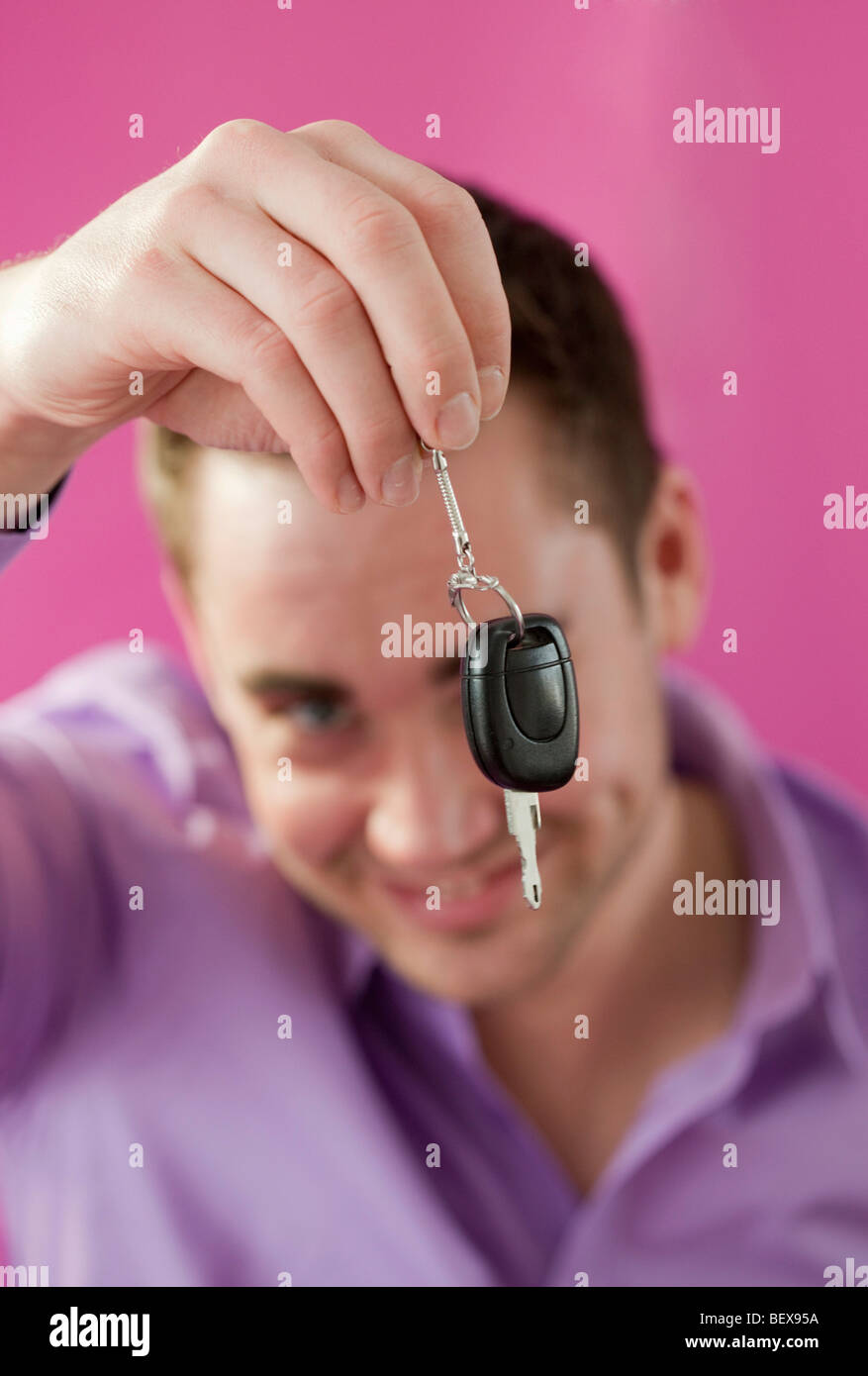 Young man holding a car key . - Stock Image