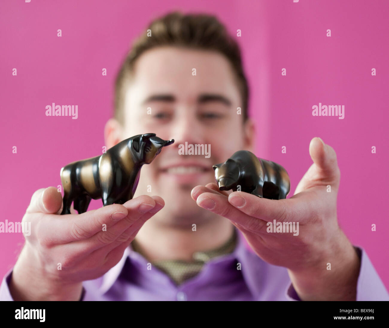 Young man holding bull and bear . - Stock Image