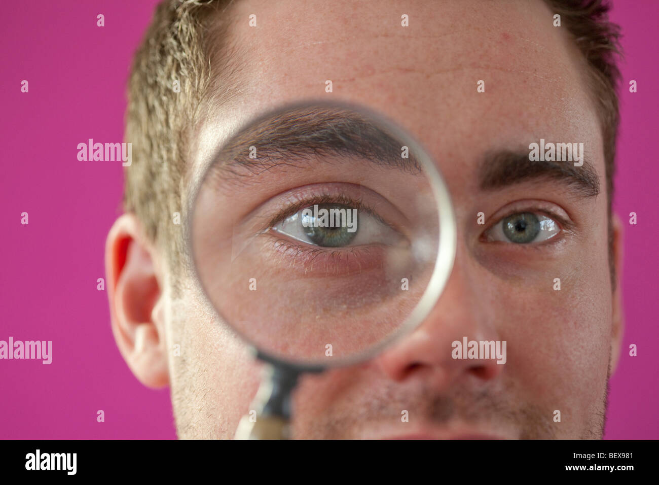 Young man looking through magnifying glass - Stock Image