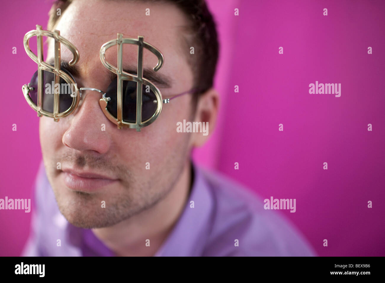 Young man waering glasses with dollar signs - Stock Image