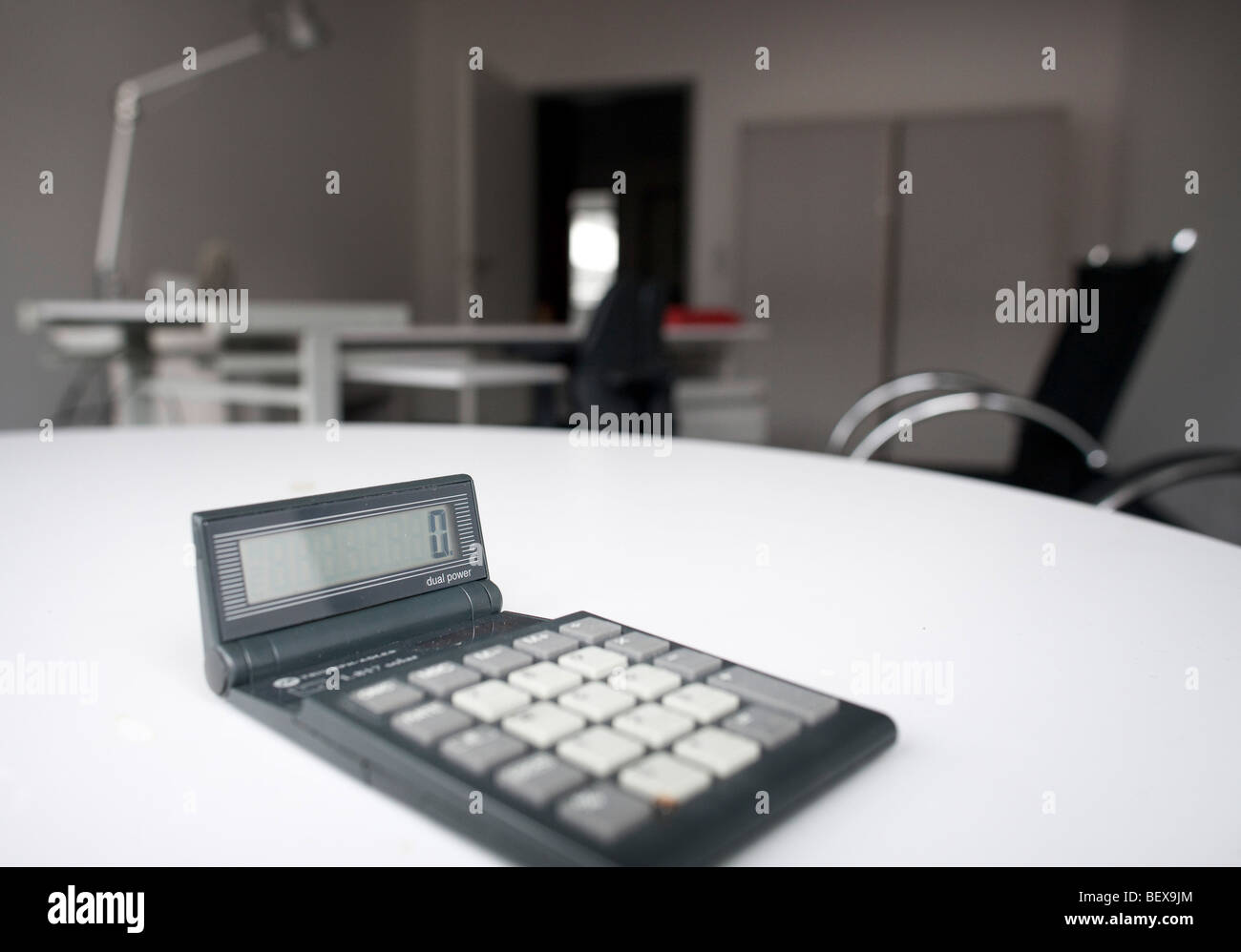Pocket calculator in an empty office - Stock Image