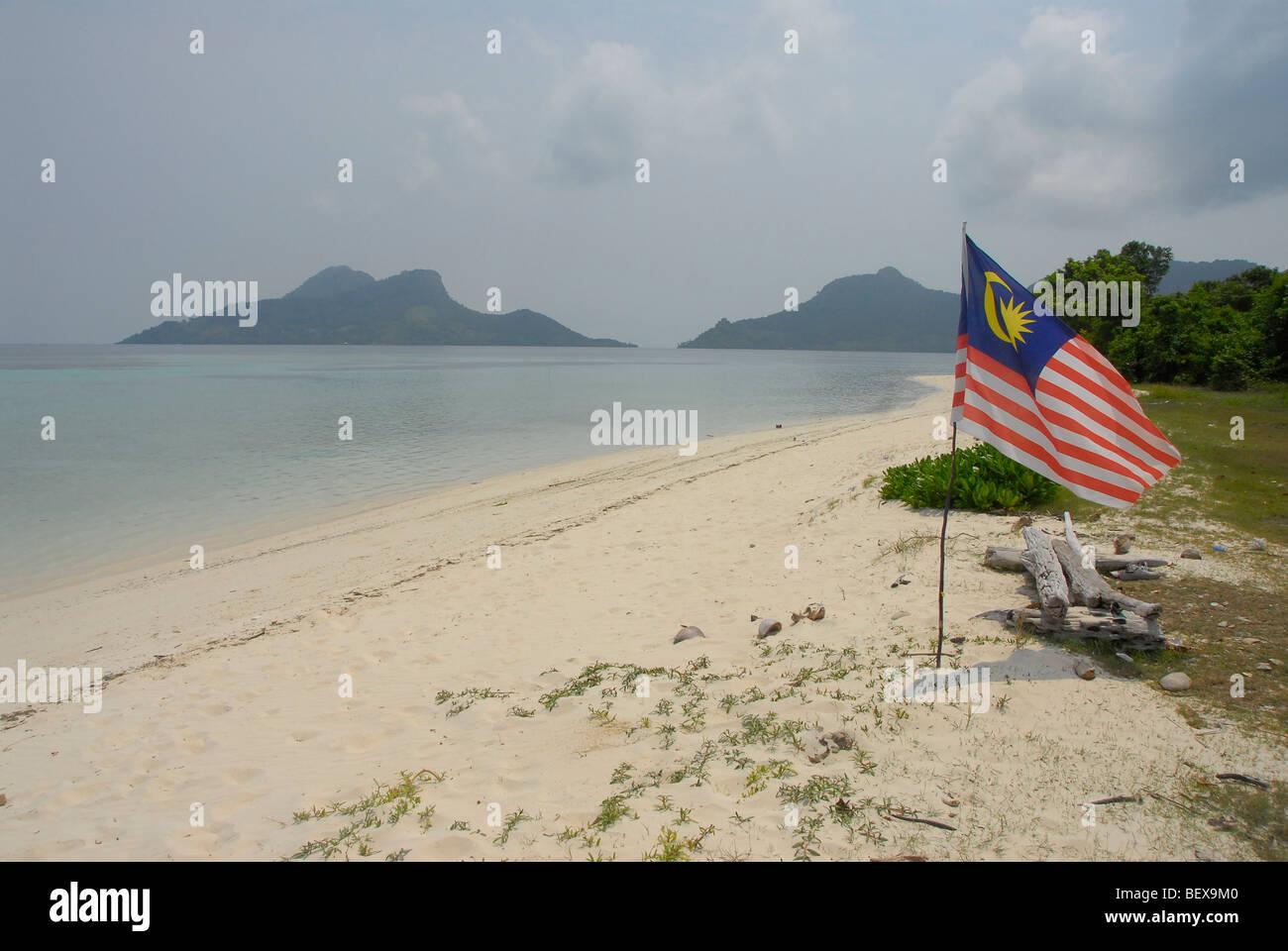 Malaysian flag fluttering on beach of Mantabuan Island, Saba Province, Borneo, Malaysia. Philippines dispute this - Stock Image