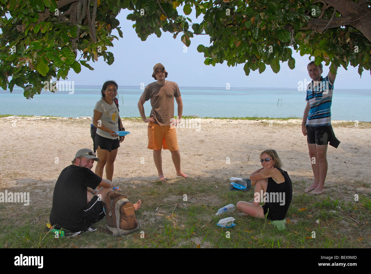 Scuba divers having a lunch break in some welcome shade on a steamy hot day in Malaysia. This island is Mantabuan - Stock Image