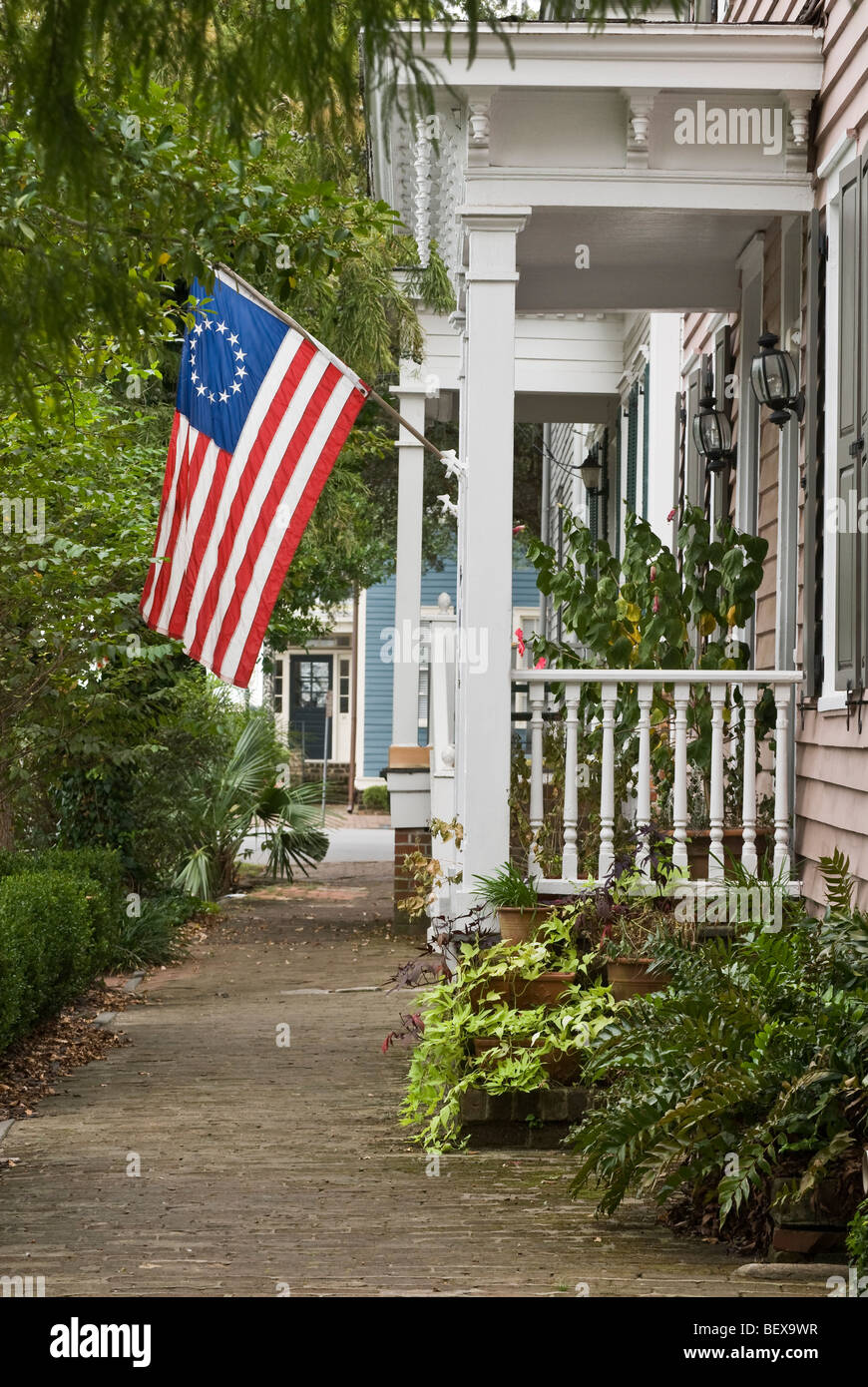American flag on porch of house, Savannah, Georgia, USA - Stock Image