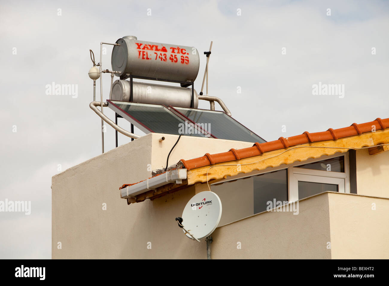 Solar water heating panels on a house roof in Teos, Turkey. - Stock Image