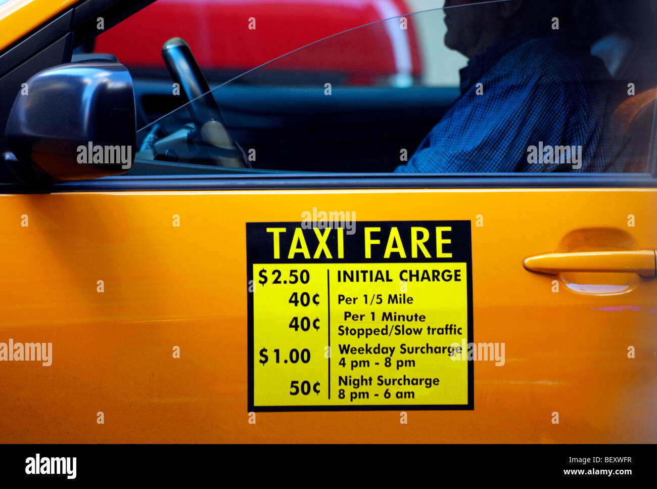 Fare information on the door of a yellow New York City taxi cab. - Stock Image