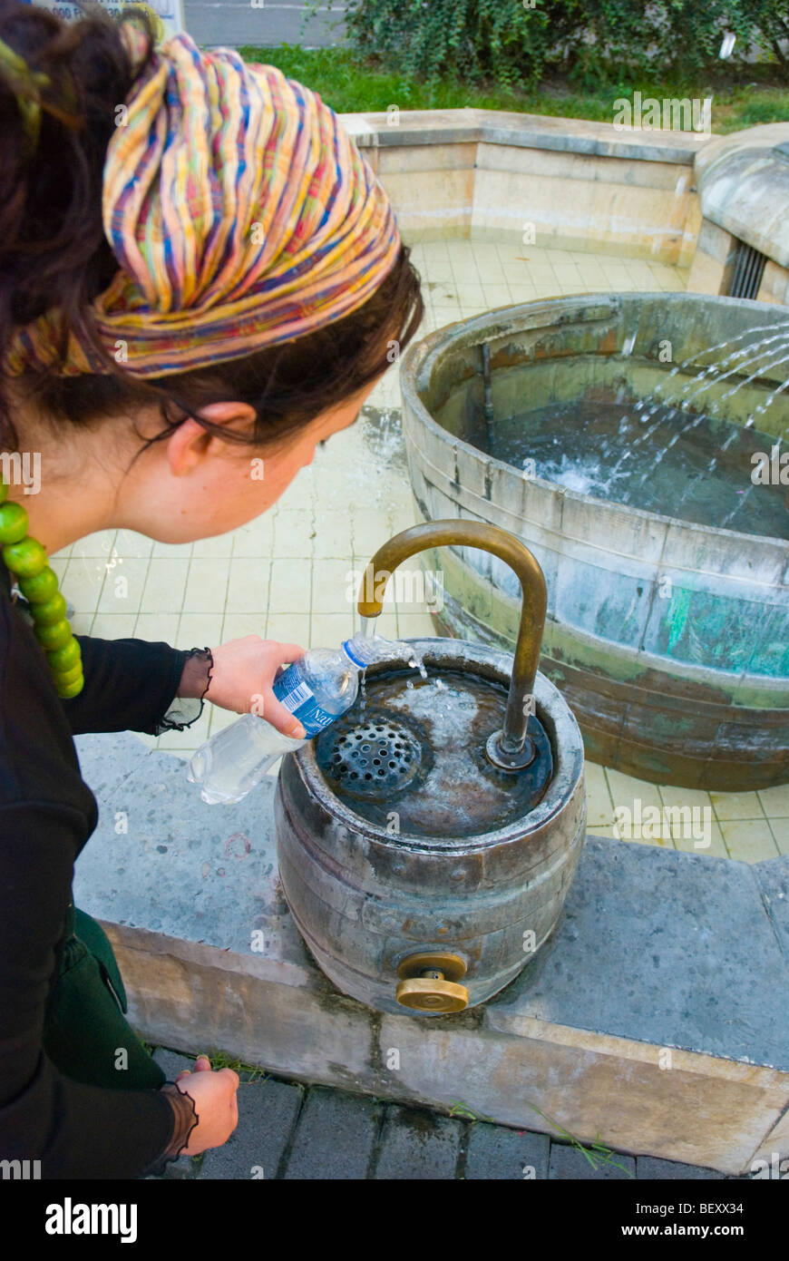 Person filling up her water bottle off a fountain in Sopron Hungary Europe - Stock Image