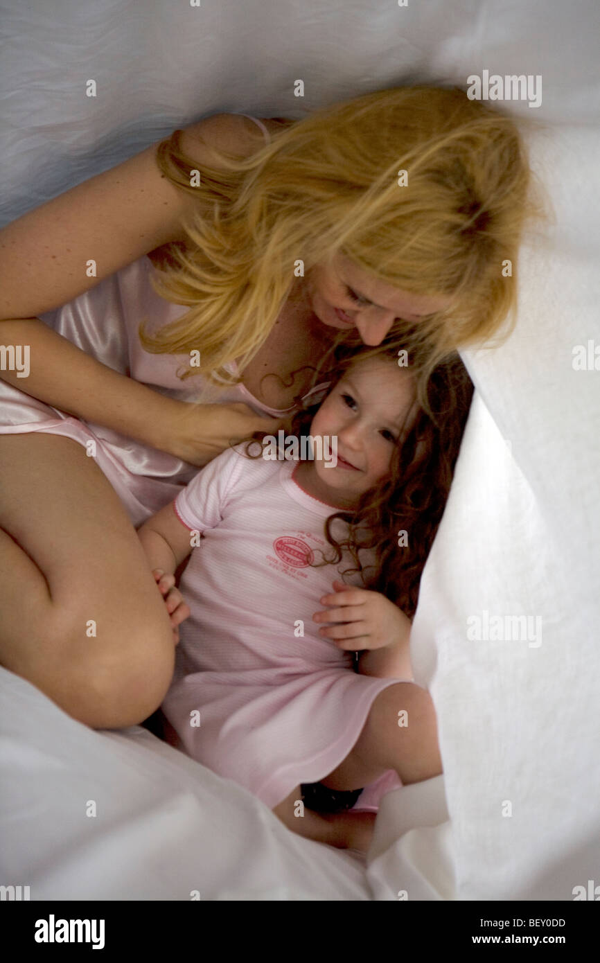 mother and daughter playing down the sheet Stock Photo