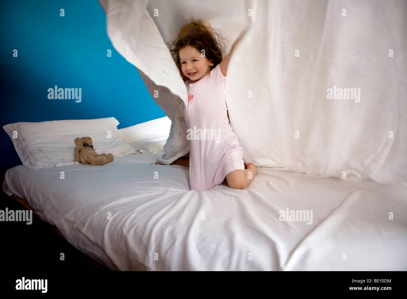 little girl playing with sheet - Stock Image