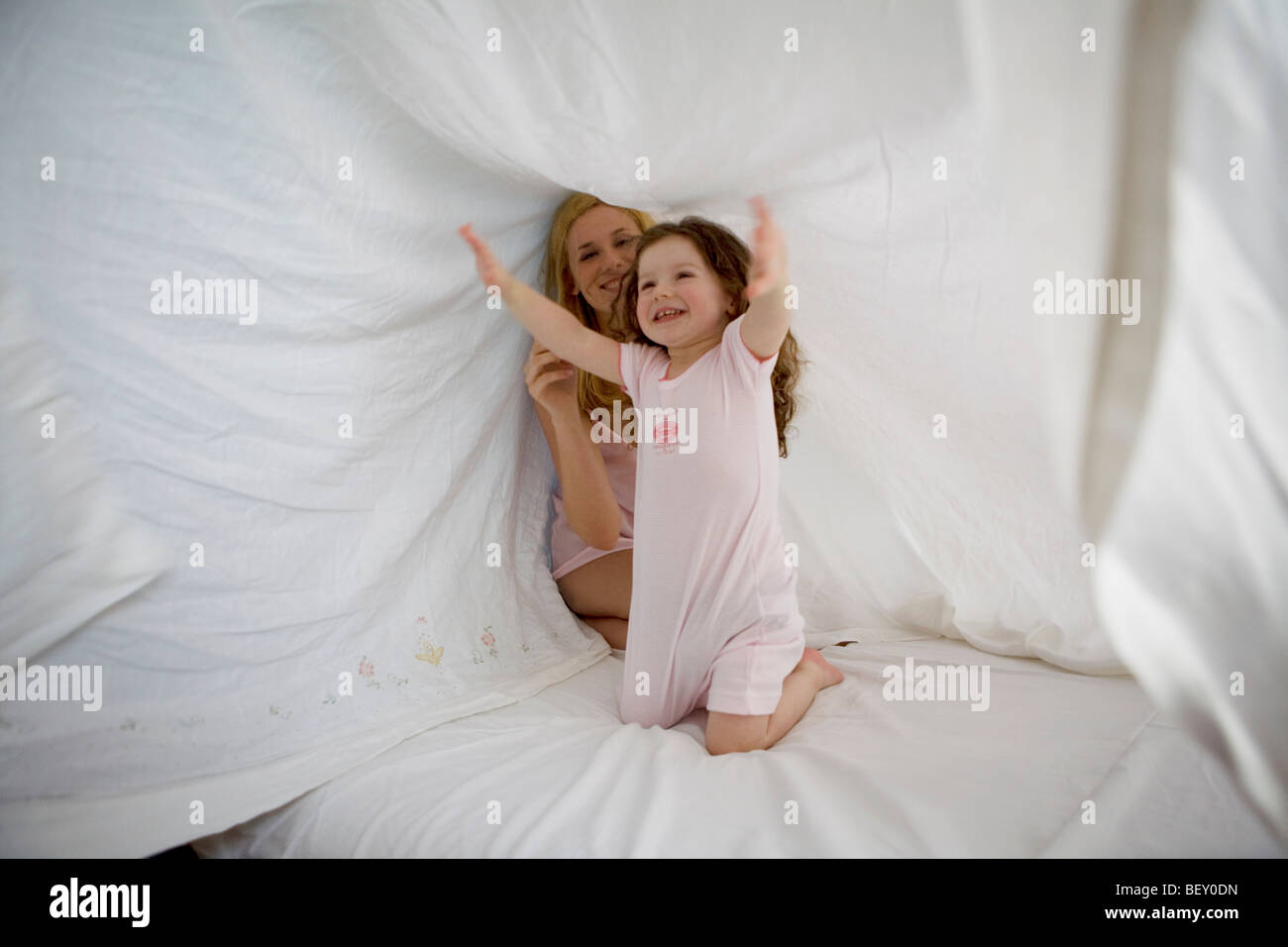 mother and daughter playing with sheet - Stock Image