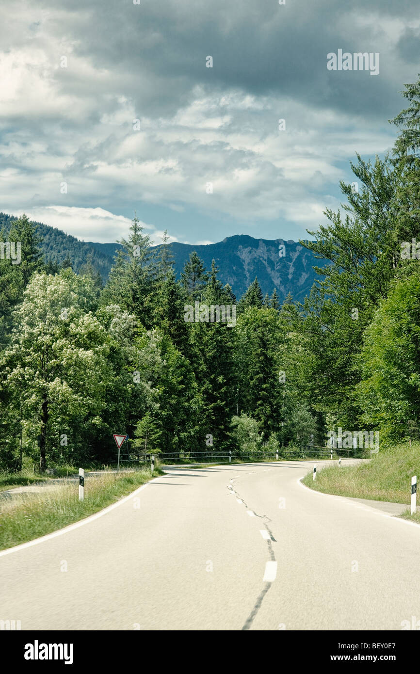 Open road through a forest towards mountains in Bavaria Germany Europe - Stock Image