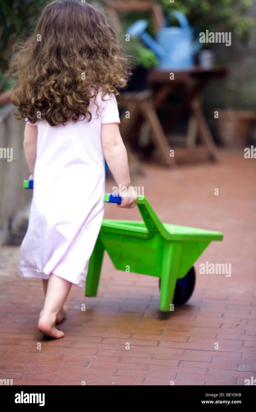 little girl plying with barrow - Stock Image