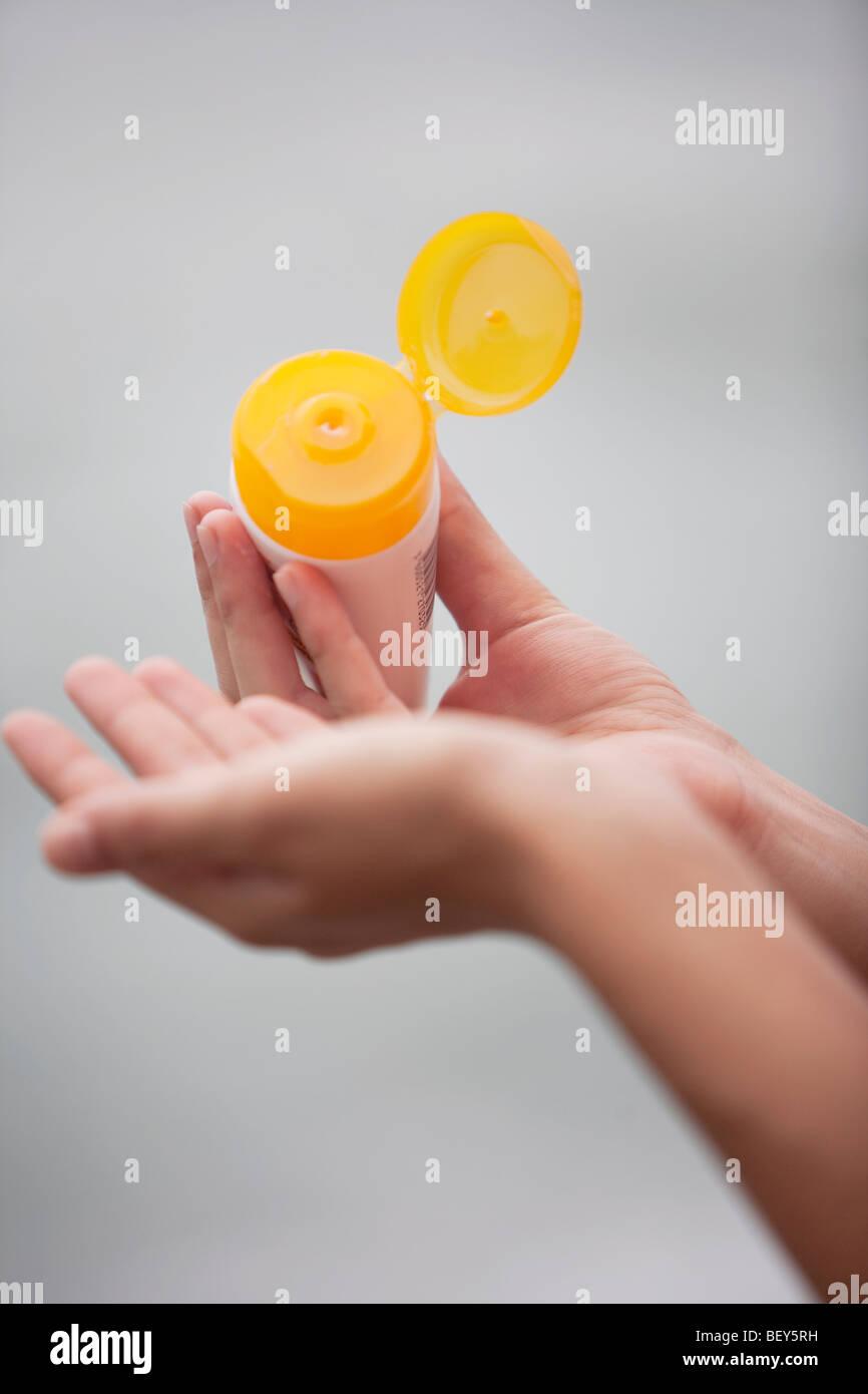 woman applying suncream to hand - Stock Image