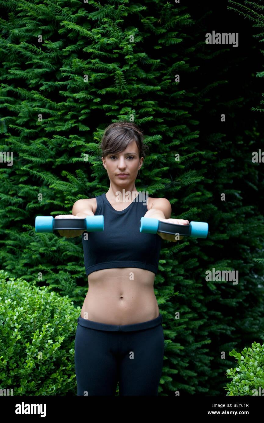 young woman lifting dumbbells - Stock Image