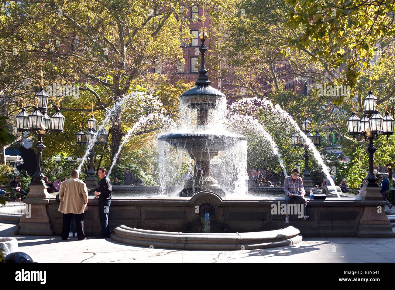 people enjoying 19th century stone Jacob Wrey Mould fountain in City hall Park New York City on a beautiful autumn - Stock Image