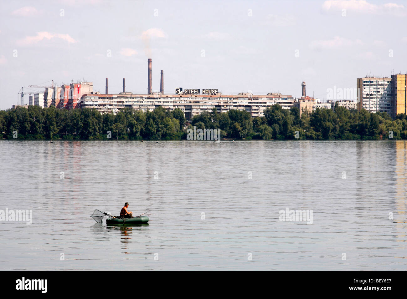 Man fishes from a boat on Dnipro river in Dnipropetrovsk Ukraine - Stock Image