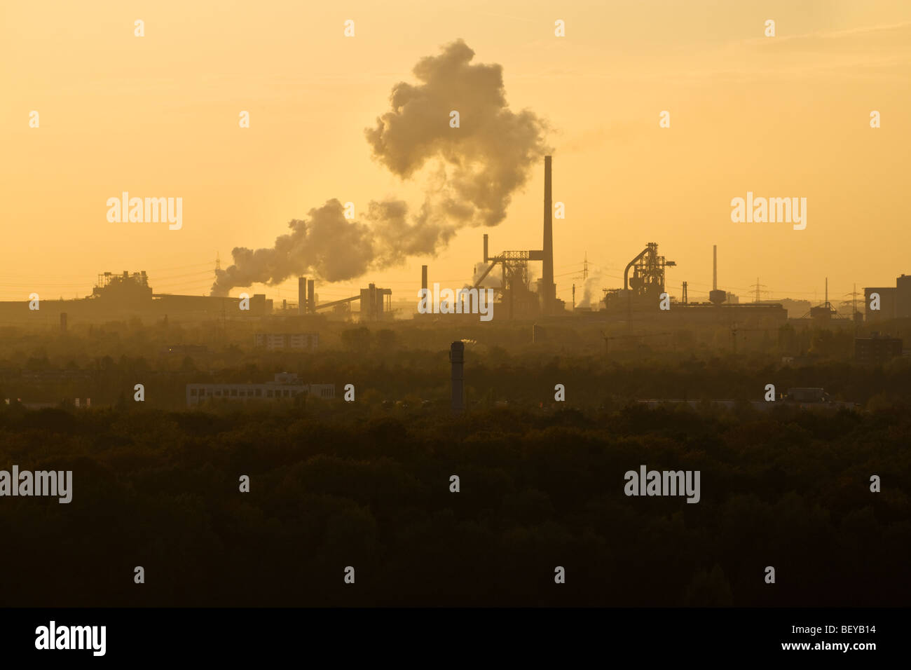 heavy industry polluting the atmosphere, sunset - Stock Image