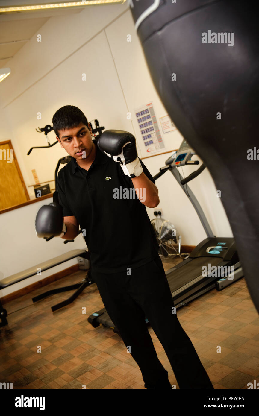 A young man practicing his boxing skills at the Big Lottery Fund supported Ethnic Youth Support Team centre, Swansea - Stock Image
