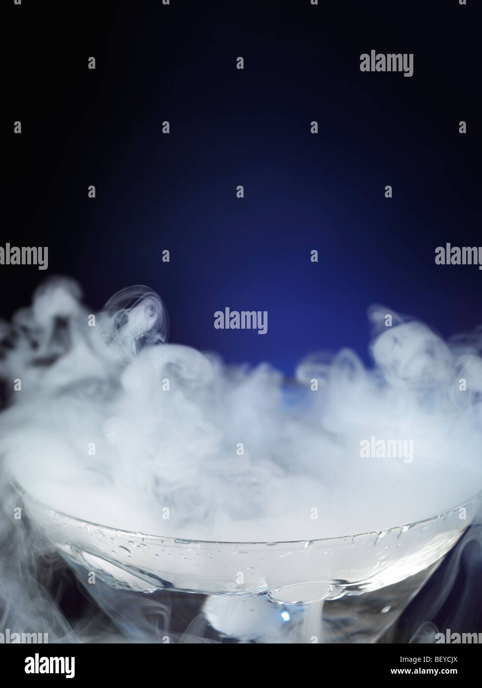 Exotic drink in a martini glass with smoke coming out of it - Stock Image