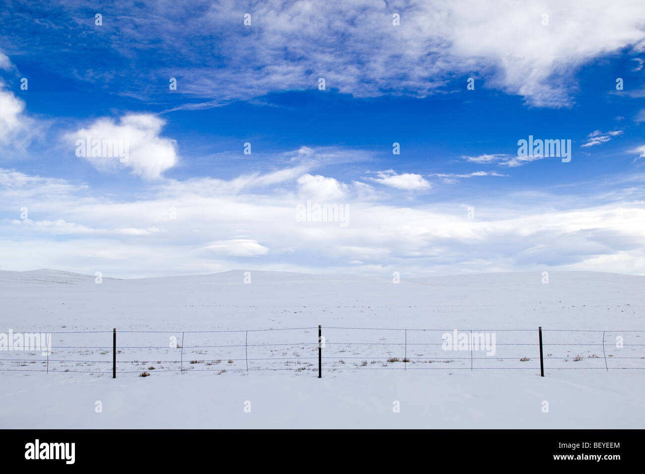 Winter landscape of clouds, snow & ranch fence near Fairplay, Colorado, USA - Stock Image