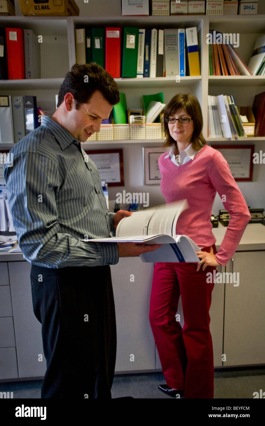 Two office workers discuss a prospectus at a financial consultant's office in Irvine, California. - Stock Image