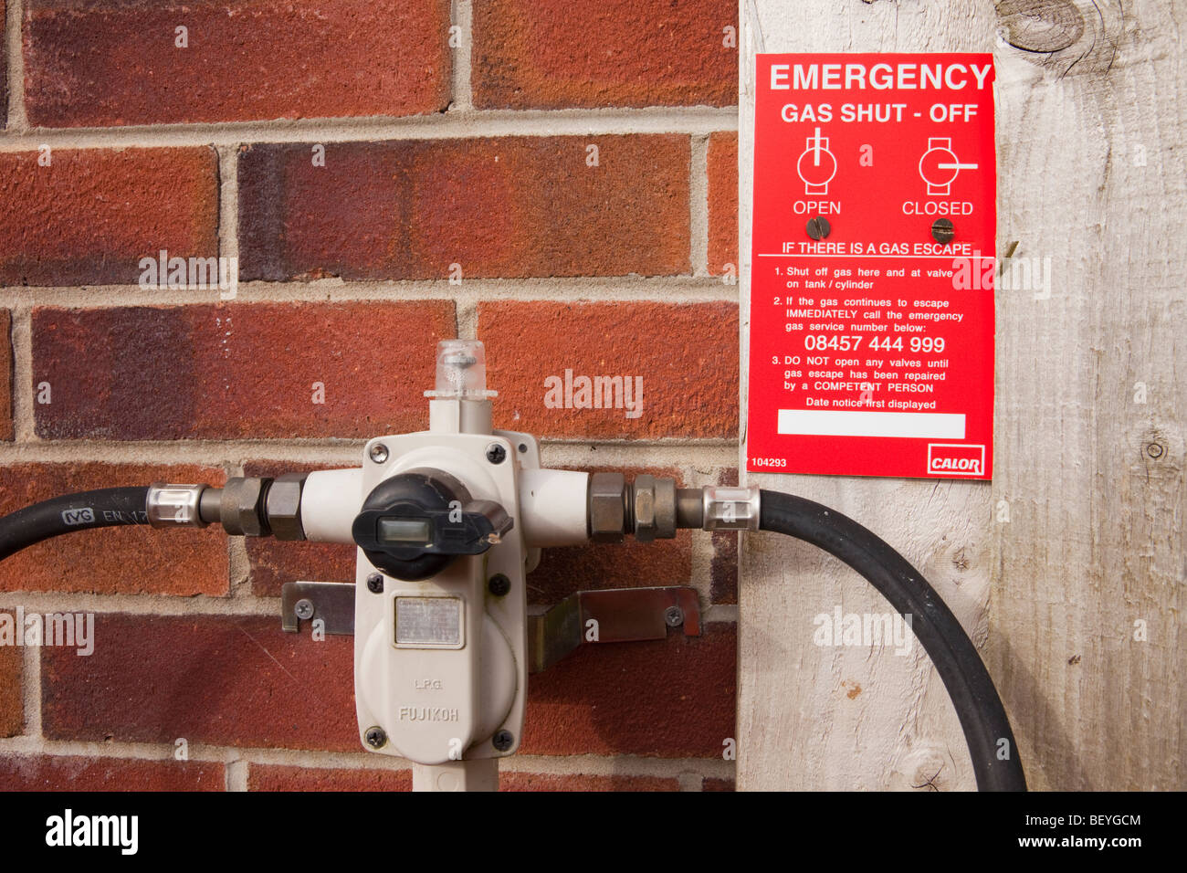 Britain, UK, Europe. Calor Gas two hose regulator valve fitting on an outside wall with emergency gas shut off instructions. - Stock Image