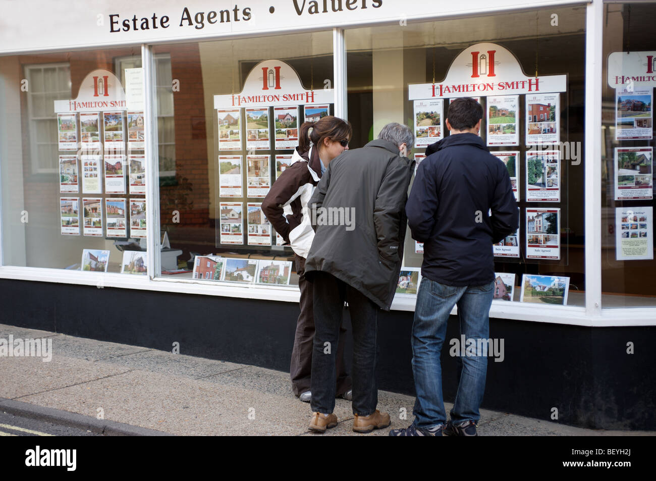 House buyers looking in estate agents window in the market town of Woodbridge, Suffolk, UK. - Stock Image