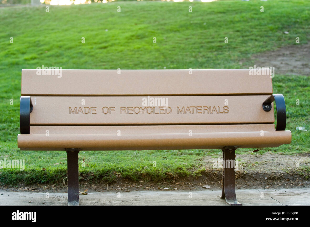 Park bench with a prominently displayed message indicating that it is manufactured with recycled materials. - Stock Image