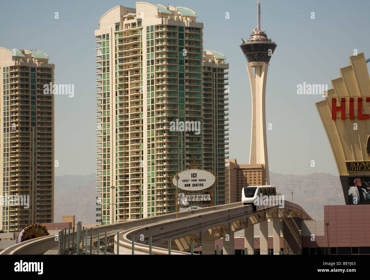 The high level monorail train glides between high rise buildings in Las Vegas, USA. - Stock Image