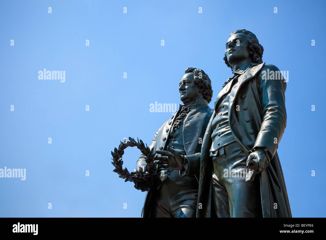 Goethe and Schiller statue against blue sky outside the German National Theatre Weimar Germany Europe - Stock Image