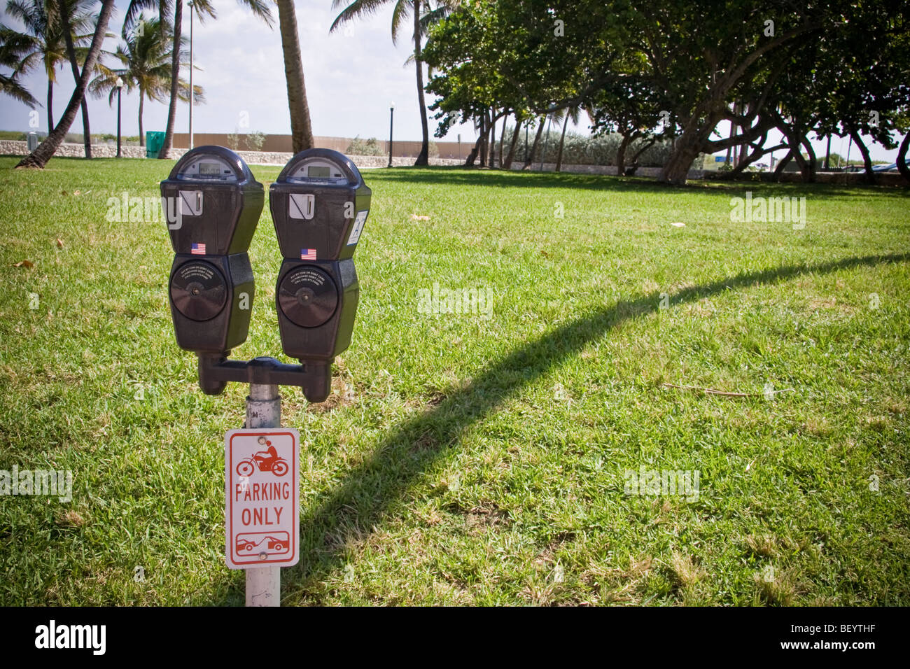Parking meter with interesting shadow cast by palm tree. Ocean Drive, Miami south beach Florida - Stock Image