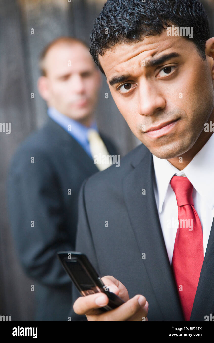 Businessman holding mobile phone with another businessman standing behind him - Stock Image