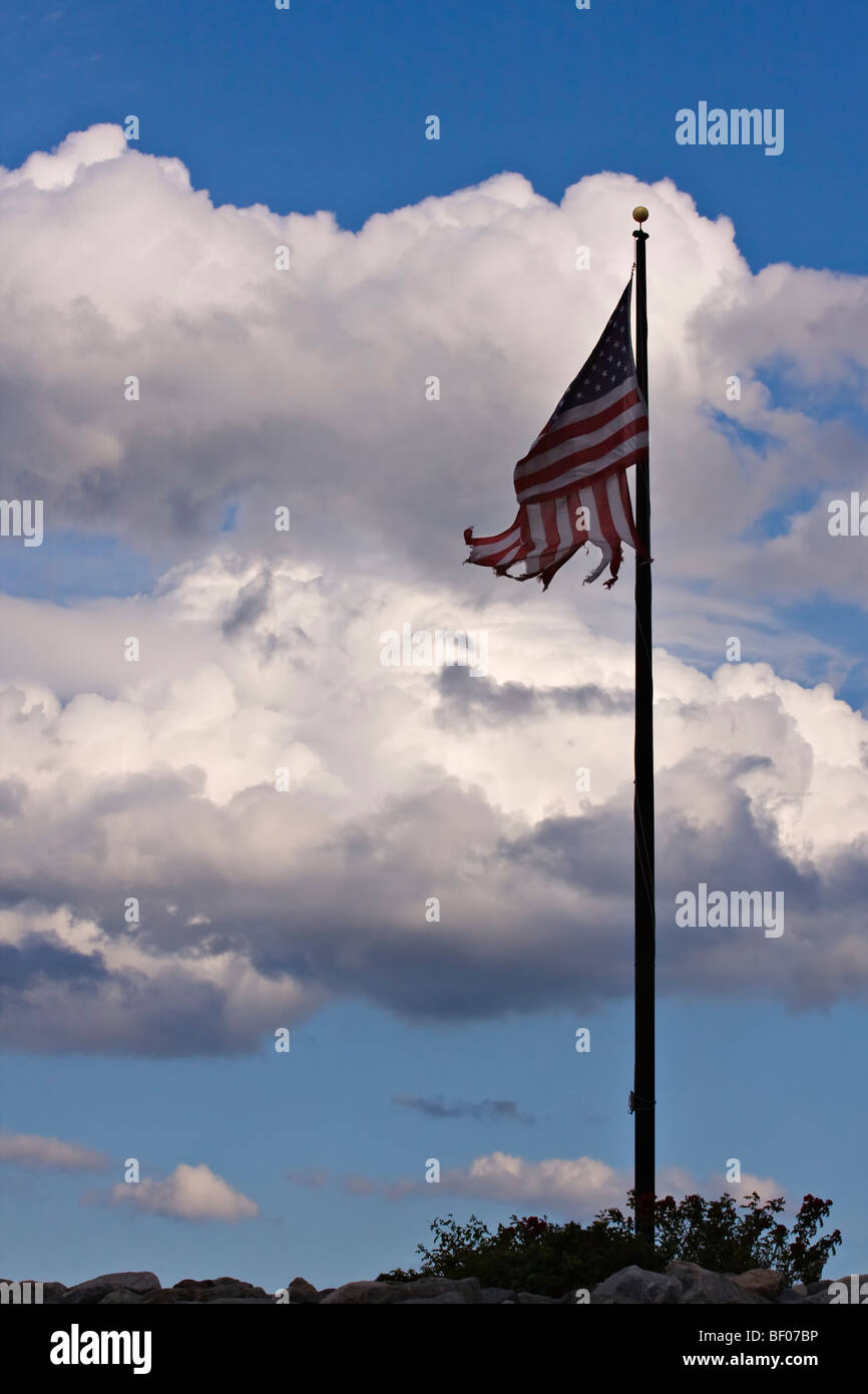 American Flag that is battered and torn on a flagpole with blue sky and clouds in background. - Stock Image