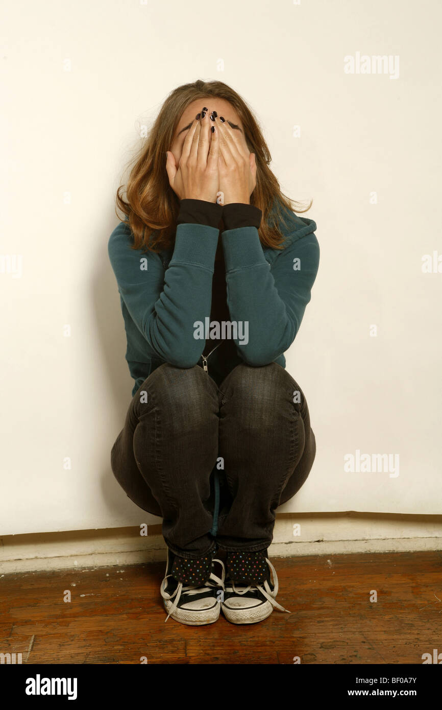 teen girl in trouble, distressed, with hands covering face. - Stock Image