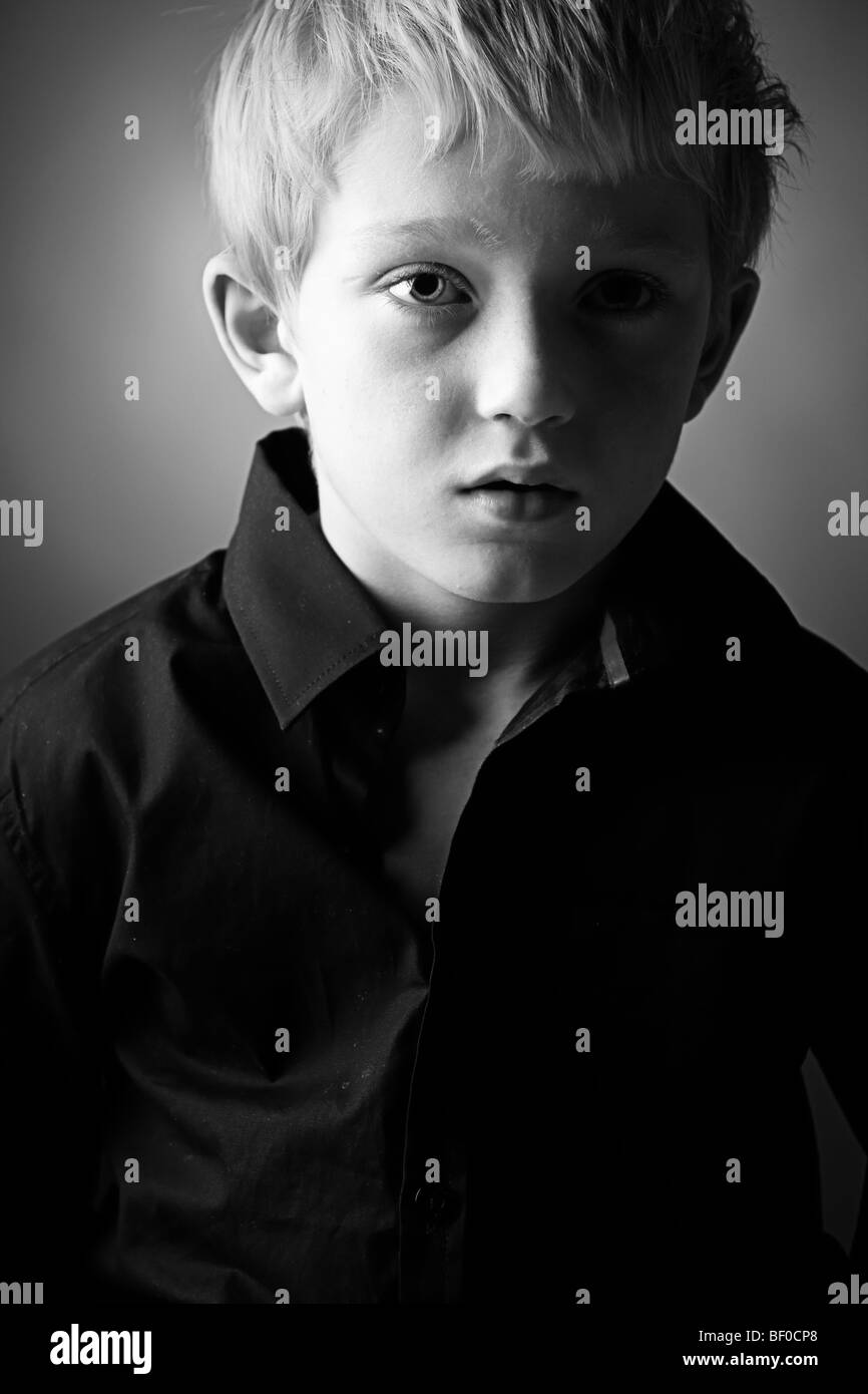 Low Key Shot of a Young Lad Looking Down - Stock Image