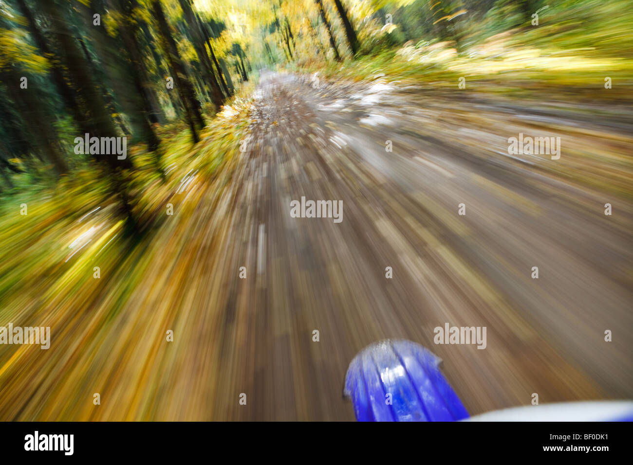 Riding dirtbike on country road in autumn scene, motion blur from drivers point of view - Stock Image