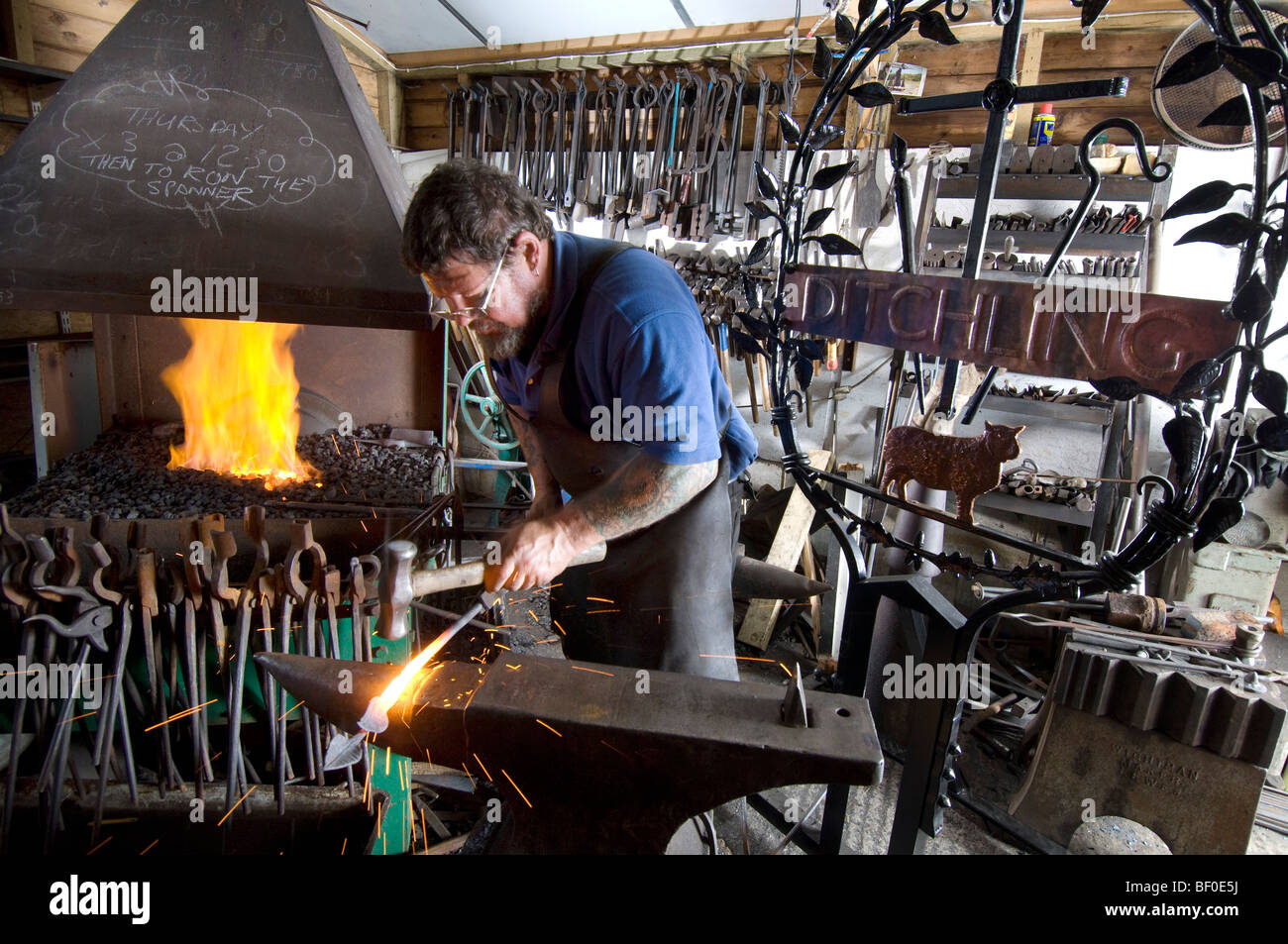 A village blacksmith forging a new sign for Ditchling in Sussex Stock Photo
