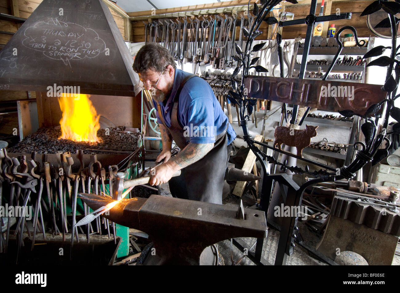 A village blacksmith forging a new sign for Ditchling in Sussex - Stock Image