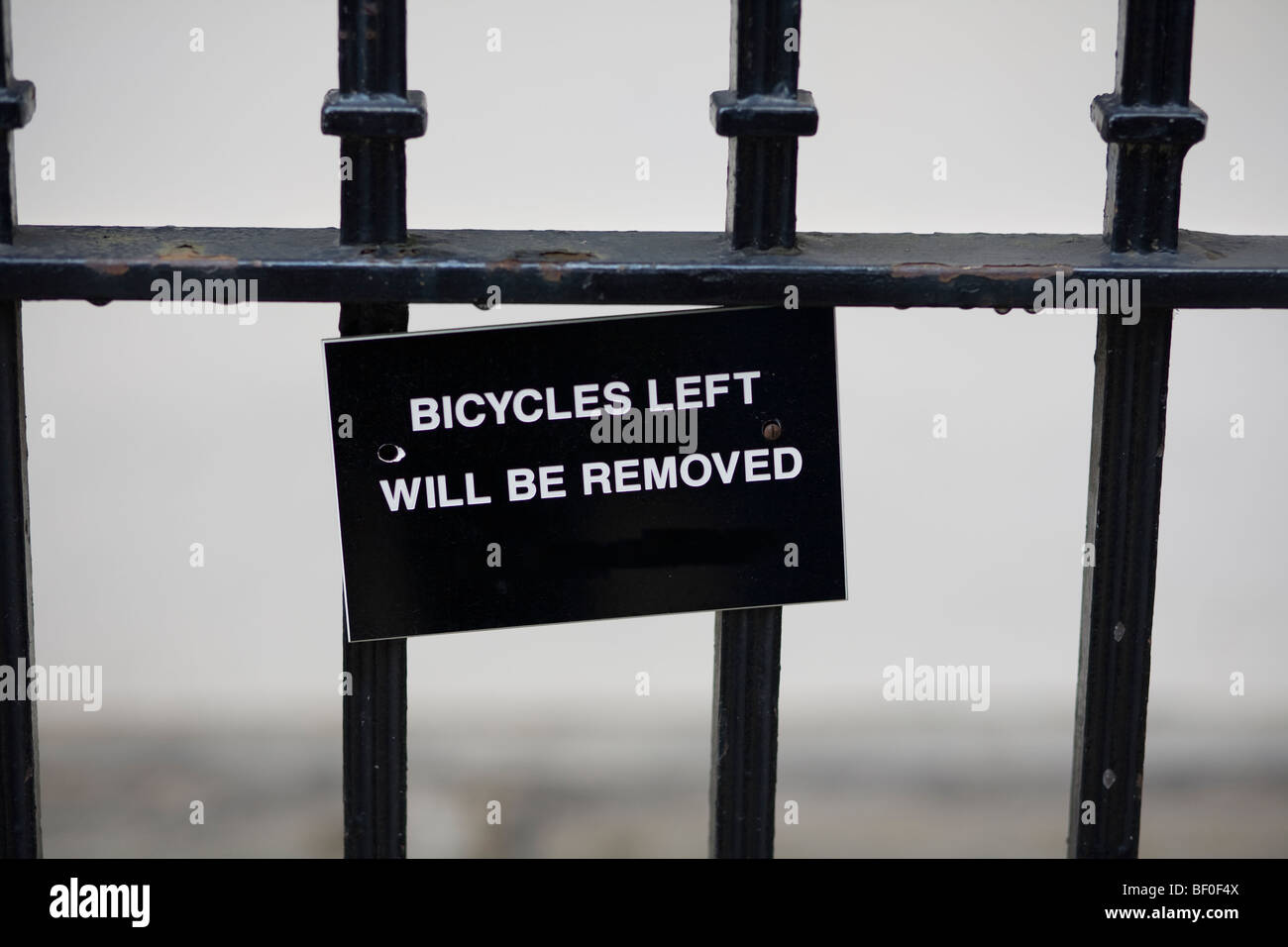 """White writing, """"Bicycles Left Will Be Removed"""", on black sign hung on black wrought iron railings. London, UK. - Stock Image"""