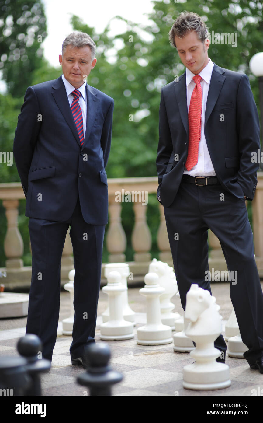 Two Businessmen Playing Giant Chess Stock Photo