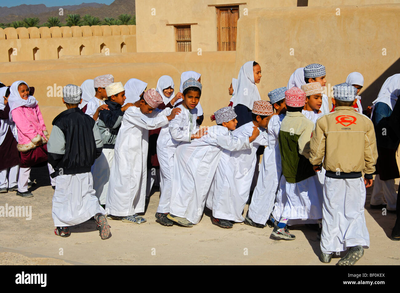 Female teacher of a mixed school class of lively boys and girls on an excursion in the Castle of Nizwa, Sultanate Stock Photo