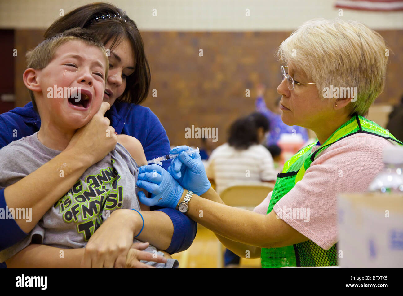 Hamtramck, Michigan - A health care worker vaccinates a boy against the H1N1 swine flu. - Stock Image