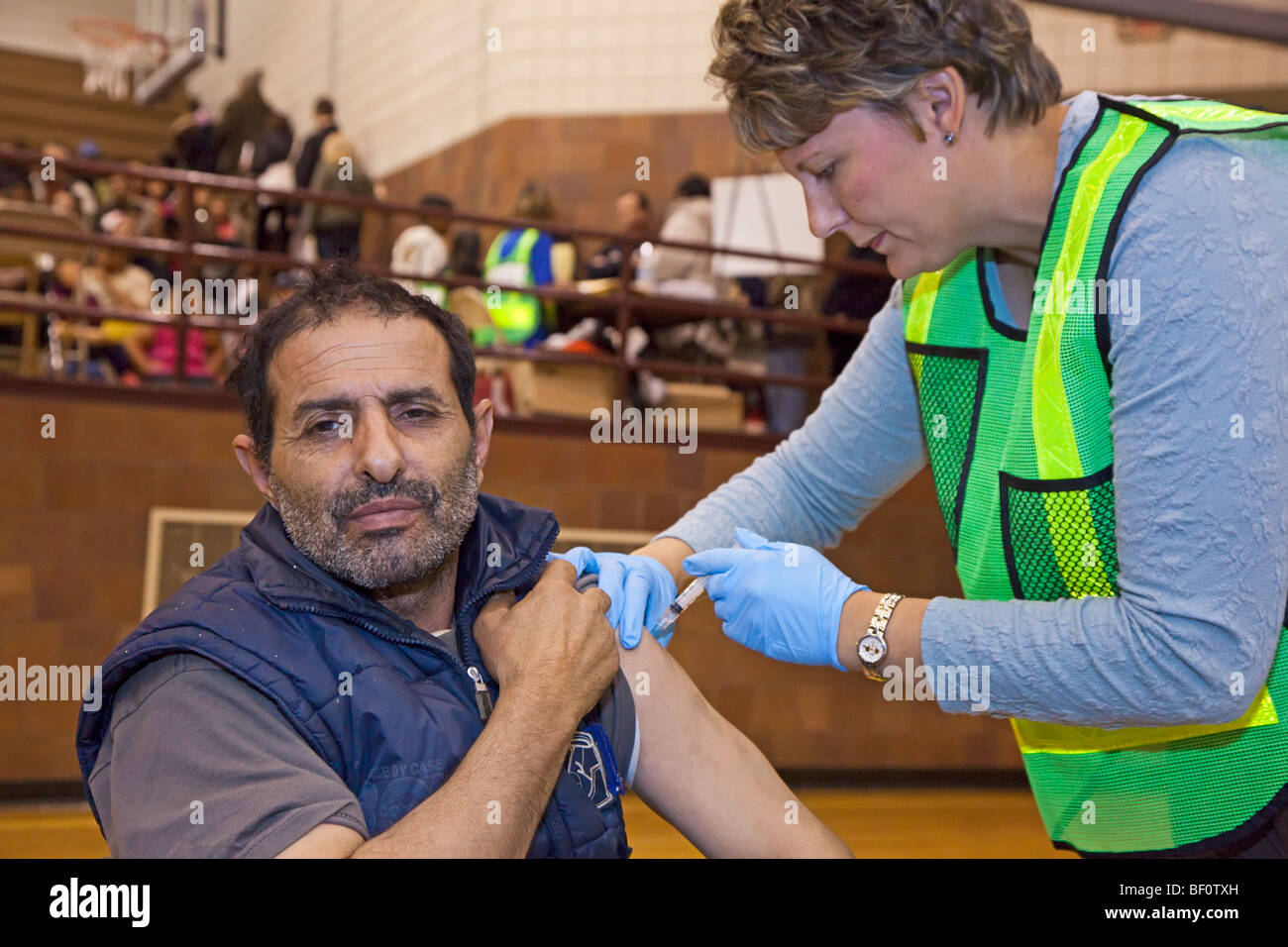 Hamtramck, Michigan - A health care worker vaccinates a man against the H1N1 swine flu. - Stock Image