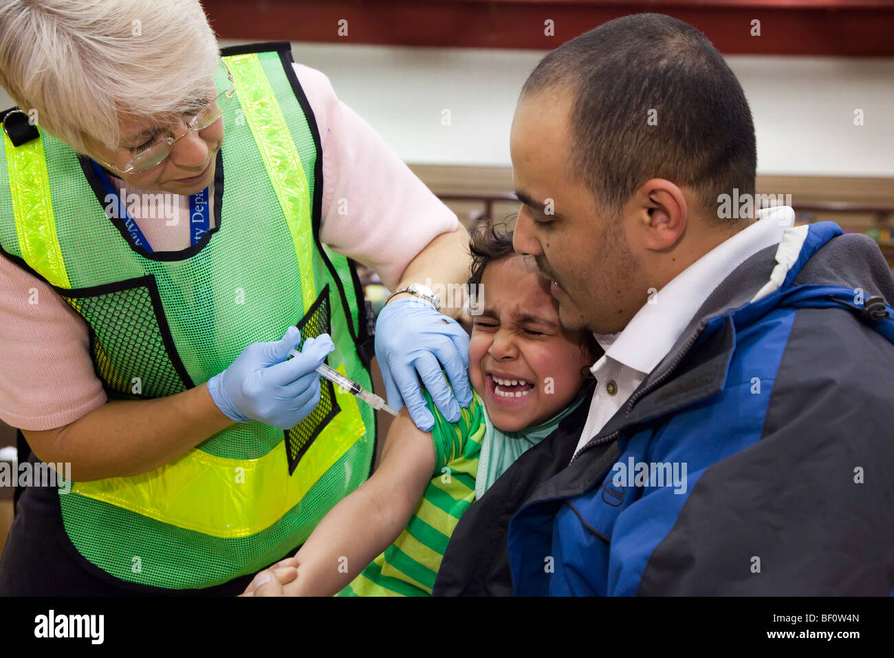 Hamtramck, Michigan - A health care worker vaccinates a girl against the H1N1 swine flu. - Stock Image