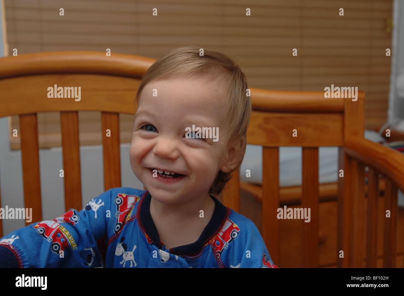 A very happy young blond boy stands in his crib smiling and laughing while wearing firetruck pajamas. - Stock Image