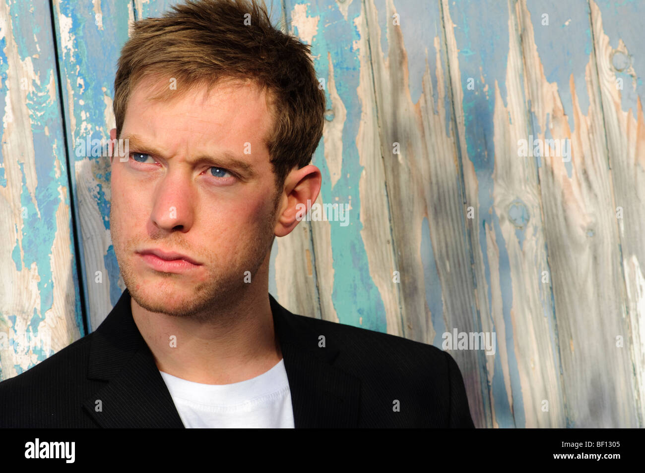 blue-eyed 30 year old man alone in front of peeling painted wooden door - looking away from the camera - Stock Image