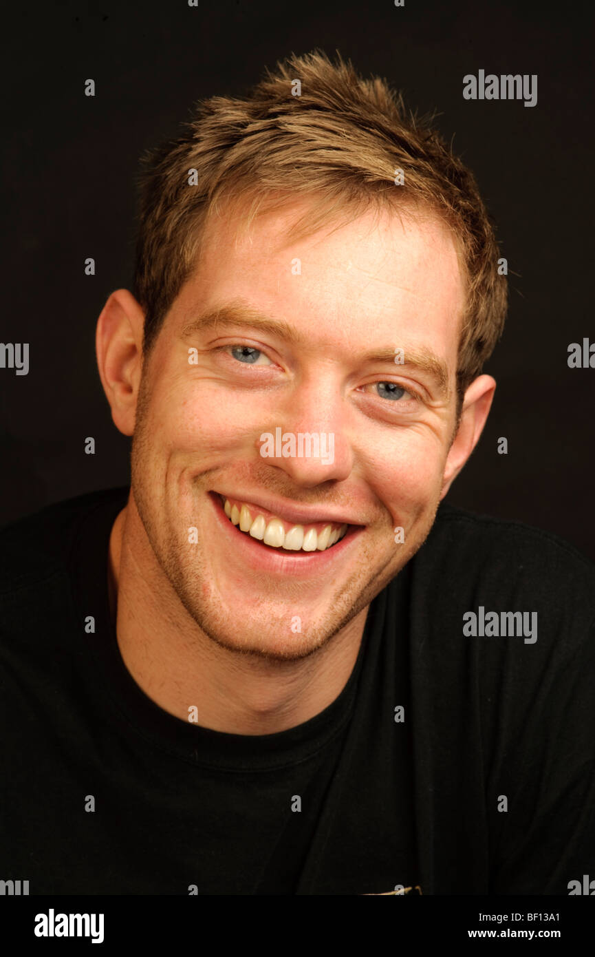 Studio portrait of a happy smiling confident healthy blue-eyed 30 year old British man - Stock Image